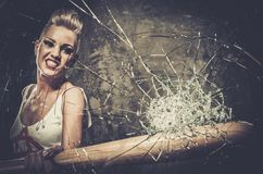 Punk girl with a bat. Punk girl breaking glass with a baseball bat stock images