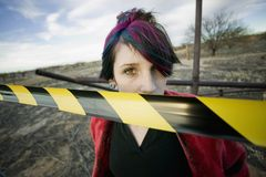 Punk Girl Behind Caution tape. Punk girl outdoors behind a strip of yellow and black caution tape Royalty Free Stock Photography