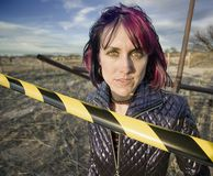 Punk Girl Behind Caution tape. Punk girl outdoors behind a strip of yellow and black caution tape Stock Photo