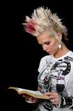 Punk Girl With Bible. Punk girl reading the Bible isolated over a black background stock images