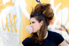 Punk girl blowing bubble gum. Outdoor royalty free stock images