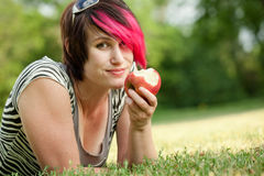 Punk girl eating an apple Stock Images