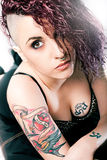 Punk girl with hair style and tattoos. Hairstyle for hairdresser. A beautiful young woman with hair shaved on one side. Red hair and wavy. Tattoos on her breast royalty free stock photography