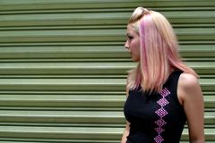 Punk Girl Posing/Green Door. Punk girl with pink hair posing in front of a green garage door Royalty Free Stock Photo