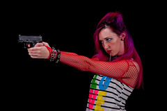 Punk girl shooting a pistol double handed. Stock Images