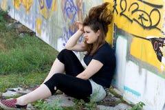Punk girl sitting near graffiti Stock Photo