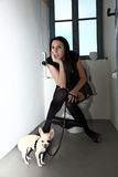 The punk girl is in the toilet with his dog Royalty Free Stock Photography