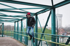 Punk guy jumping on a bridge Stock Photo