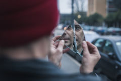 Punk guy looking at himself in a shattered mirror Royalty Free Stock Photography