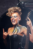 Punk impressionato della donna che mostra i corni del metallo fotografia stock libera da diritti