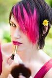Punk kvinna som sätter på makeup Arkivbild