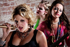 Punk Rock Band. All-girl punk rock band performs in front of a brick background Royalty Free Stock Photos