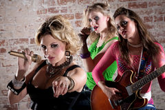 Punk Rock Band. All-girl punk rock band performs in front of a brick background Royalty Free Stock Image