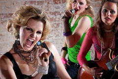 Punk Rock Band. All-girl punk rock band performs in front of a brick background Stock Photos