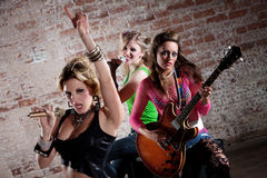 Punk Rock Band. All-girl punk rock band performs in front of a brick background Stock Image