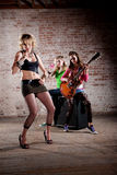 Punk Rock Band. All-girl punk rock band performs in front of a brick background Stock Photo