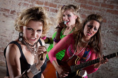 Punk Rock Band. All-girl punk rock band performs in front of a brick background Royalty Free Stock Images