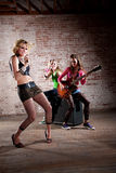 Punk Rock Band. All-girl punk rock band performs in front of a brick background Stock Images