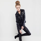 Punk rock blond young woman in latex and high heels. Sexy beautiful girl in leather with dreadlocks hairstyle. punk rock blond young woman in latex and high Stock Photos