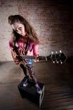 Punk Rock Girl. Punk rocker girl alone with her guitar Stock Photo