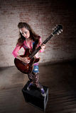 Punk Rock Girl. Punk rocker girl alone with her guitar Royalty Free Stock Image