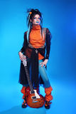 Punk rock girl guitarist posing over blue studio background. Tre Stock Images