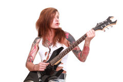 Punk rock guitarist girl. Studio shot of young attractive redhead punk girl with multiple tattoo playing electric guitar and singing, taken on white background Stock Photography