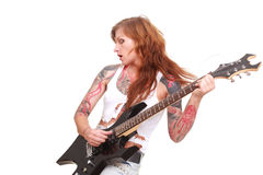 Punk rock guitarist girl. Studio shot of young attractive redhead punk girl with multiple tattoo playing electric guitar and singing, taken on white background Stock Photos