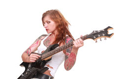 Punk rock guitarist girl. Studio shot of young attractive redhead punk girl with multiple tattoo playing electric guitar and singing, taken on white background Royalty Free Stock Photos