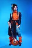 Punk rock-Mädchengitarrist, der über blauem Studiohintergrund aufwirft Tre Stockbilder