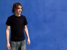 Punk Rocker. Against blue wall Stock Photos