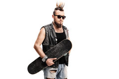 Punk rocker holding a skateboard. And looking at the camera isolated on white background Stock Photos