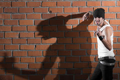 Punk rocker stylish man. In the white T-shirt and black jeans with red urban brick wall background Stock Image
