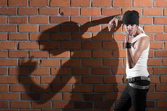 Punk rocker stylish man. In the white T-shirt and black jeans with red urban brick wall background Royalty Free Stock Photos