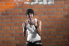 Punk rocker stylish man. In the white T-shirt and black jeans with red urban brick wall background Stock Photos