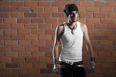 Punk rocker stylish man. In the white T-shirt and black jeans with red urban brick wall background Stock Photo