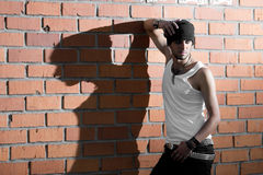 Punk rocker stylish man. In the white T-shirt and black jeans with red urban brick wall background Royalty Free Stock Photography