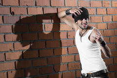 Punk rocker stylish man. In the white T-shirt and black jeans with red urban brick wall background Stock Photography