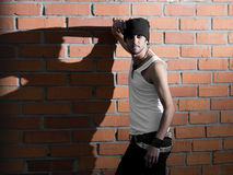 Punk rocker stylish man. In the white T-shirt and black jeans with red urban brick wall background Royalty Free Stock Images