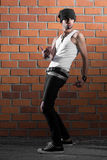 Punk rocker stylish man. In the white T-shirt and black jeans with red urban brick wall background Stock Images
