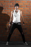 Punk rocker stylish man. In the white T-shirt and black jeans with red urban brick wall background Royalty Free Stock Image