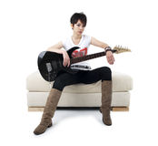 Punk Rockstar. Holding guitar sitting on sofa isolated in white Stock Images