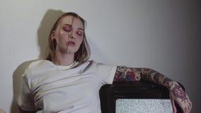 Punk tattooed girl sitting near working static tv set in dark room. Punk tattooed caucasian girl with glitter on face in white shirt sitting near working static stock video