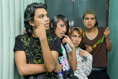 Punk teen gang. Group of 4 punk, goth or emo teenagers (Asian and Indian) hanging out in a corridor indoors showing a tough attitude as being a youth gang. Focus royalty free stock photos