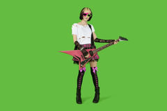 Punk woman with guitar over green colored background Royalty Free Stock Photography