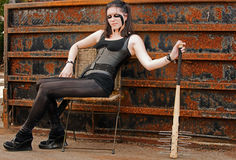Punk woman relaxes while keeping her bat handy Royalty Free Stock Photography