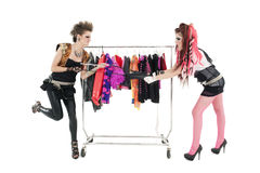 Punk women pulling dress in front of clothes rack over white background Royalty Free Stock Photo