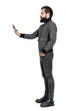 Punker alla moda serio in rivestimento grigio che prende la foto del selfie Vista laterale Fotografia Stock Libera da Diritti