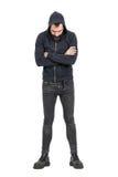 Punker duro in maglietta felpata incappucciata nera con le armi attraversate che guardano giù Fotografie Stock