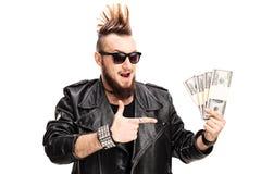 Punker em um casaco de cabedal que guarda o dinheiro e apontar imagens de stock royalty free